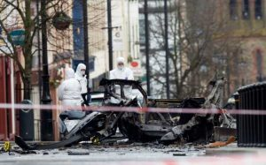 Police forensic officers inspect the aftermath of a suspected car bomb explosion in Derry CREDIT: PAUL FAITH/AFP