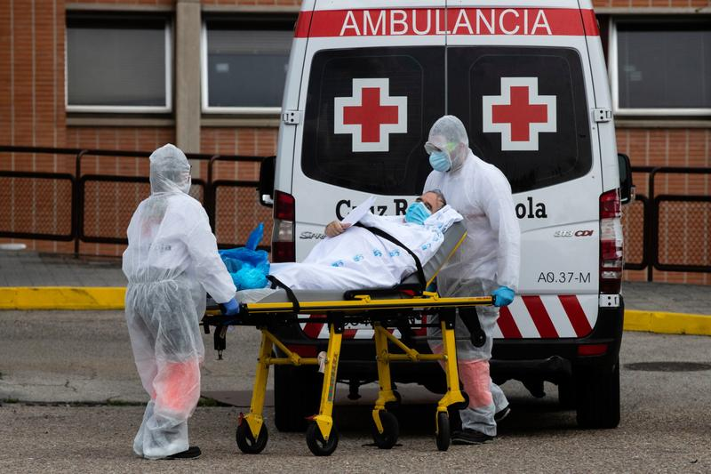 Emergency workers wearing full protective suits transport a patient in Leganes, Spain